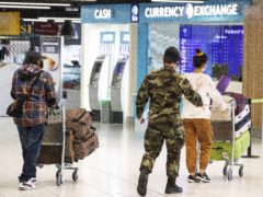A member of the defence forces escorts passengers from Terminal 1 arrivals hall at Dublin Airport (Brian Lawless/PA)