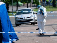 A forensics officer takes photographs at the scene on College Road, Kingstanding (PA)