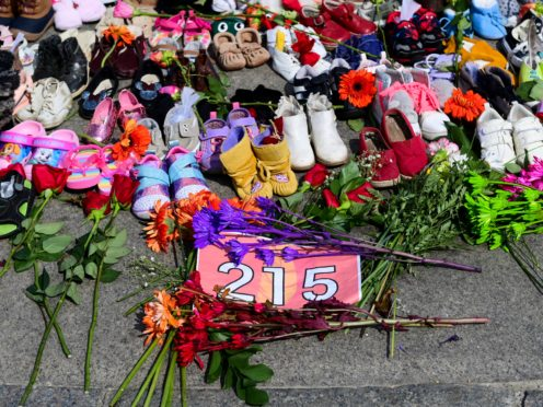 Flowers, children's shoes and other items at a memorial at the Eternal flame on Parliament Hill in Ottawa (Sean Kilpatrick/The Canadian Press via AP)