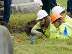 Oklahoma state archaeologist Kary Stackelbeck, left, examines the digging site as excavation begins at Oaklawn Cemetery in a search for victims of the Tulsa Race Massacre (Sue Ogrocki/AP)