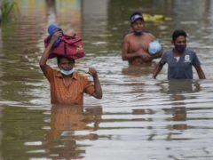 Sri Lankans wade through an inundated street following heavy rainfall (Eranga Jayawardena/AP)