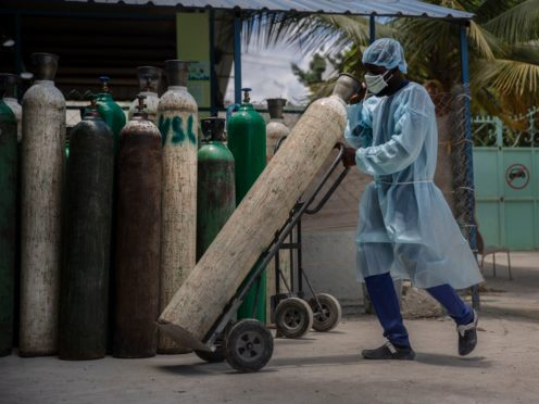 A hospital emplyee wearing protective gear as a precaution against the spread of the new coronavirus, transports oxygen tanks, in Port-au-Prince, Haiti (Joseph Odelyn/AP)