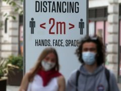 Two people wearing masks in front of a social distancing sign in Regent Street, London (Luciana Guerra/PA)