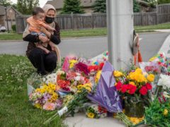 Nafisa Azima and her daughter Seena Safdari attend a memorial at the location where a family of five was hit by a driver, in London, Ontario (Brett Gundlock/AP)