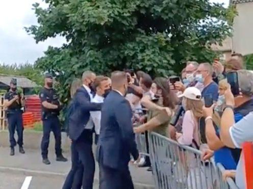 President Emmanuel Macron, centre, is slapped by a man (BFM TV via AP)