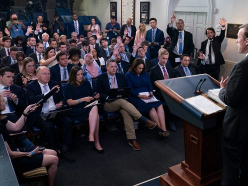 Journalists raise their hands to ask a question in the White House (Evan Vucci/AP)