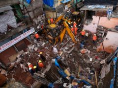 Rescuers clear debris after a building collapsed in Mumbai (Rafiq Maqbool/AP)