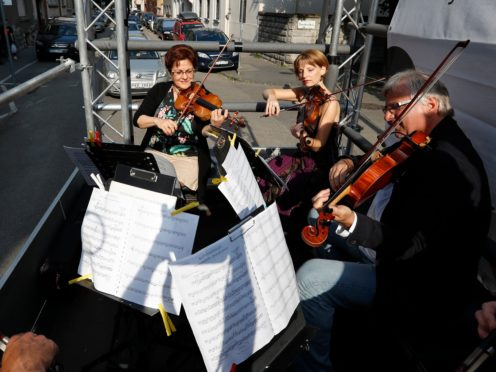 Members of the Budapest Festival Orchestra play music on the back of a truck (Laszlo Balogh/AP)