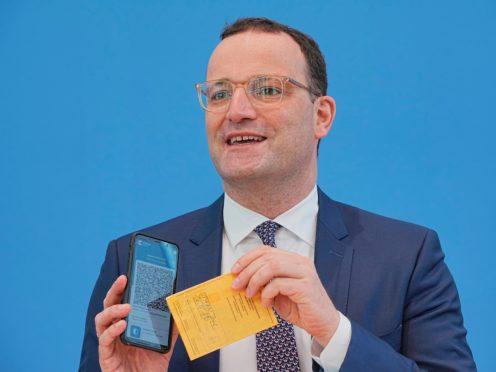 Jens Spahn shows off the new app alongside an old paper certificate (Michael Kappeler/dpa via AP)