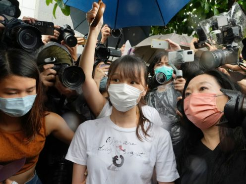 Agnes Chow, center, a prominent pro-democracy activist who was sentenced to jail last year for her role in an unauthorized protest, is released in Hong Kong Saturday, June 12, 2021. Chow rose to prominence as a student leader in the now defunct Scholarism and Demosisto political groups, alongside other outspoken activists such as Joshua Wong and Ivan Lam. (AP Photo/Vincent Yu)