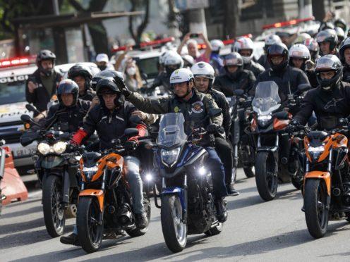 Brazil's President Jair Bolsonaro, centre, waves from his motorbike (Marcelo Chello/AP)