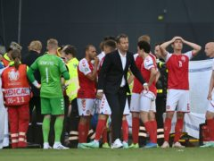 Denmark's players look on anxiously as team-mate Christian Eriksen received life-saving resuscitation treatment during Saturday's Euro 2020 match against Finland (Stuart Franklin/AP)