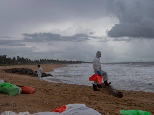 Sri Lankan sailors clean up debris from the container ship on beaches near Colombo (Eranga Jayawardena/AP)