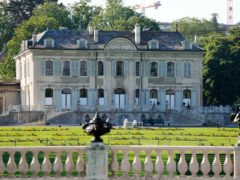 A police officer sits in front of the Villa la Grange in Geneva ahead of the summit (Markus Schreiber/AP)