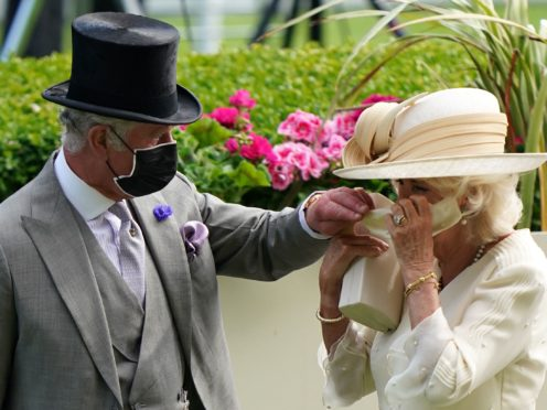 The Prince of Wales helps the Duchess of Cornwall with her mask during day two of Royal Ascot at Ascot Racecourse (Andrew Matthews/PA)