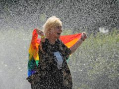 A woman with a rainbow flag cools off in a sprinkler ahead of the Equality Parade (Czarek Sokolowski/AP)