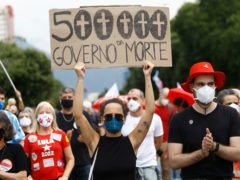 A woman wearing a protective face mask holds a sign (Bruna Prado/AP)
