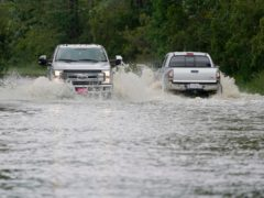 Pickup trucks pass each other on a flooded road in Biloxi, Mississippi. Thirteen people died in the southern US after incidents linked to Tropical Depression Claudette (Rogelio V Solis/AP)