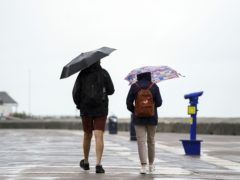 People use umbrellas to shelter from the rain on the seafront in Southsea, Hampshire (PA/Steve Parsons).