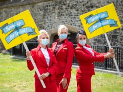 Virgin cabin crew join a protest by members of the travel industry on College Green, Westminster, central London, during a Travel Day of Action (Dominic Lipinski/PA)