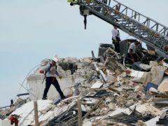 救援人员在坍塌的尚普兰塔废墟中寻找生命迹象(琳恩·斯拉迪/美联社)