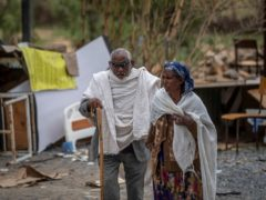 A woman leads a blind man to a visiting doctor amid a devastated area in the Tigray region of northern Ethiopia (AP)