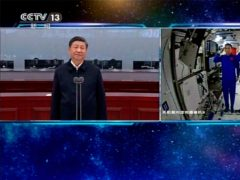 The three Chinese astronauts salute as they talk with President Xi Jinping, at China's new space station on Wednesday (CCTV/AP)