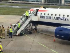 Former Paralympian James Brown lying on top of a British Airways plane at City Airport, London (Extinction Rebellion/PA)