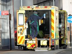 A worker in PPE cleans the back of an ambulance after dropping off a patient at the Royal London Hospital during the second wave of coronavirus in January (Yui Mok/PA)