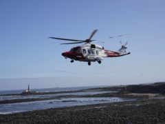An HM coastguard helicopter lifts off to airlift a person to safety at Old Hartley near Whitley Bay (Owen Humphreys/PA)
