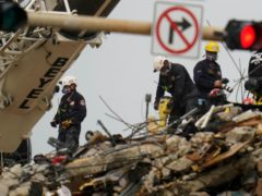 Search and rescue personnel work atop the rubble at the Champlain Towers South condo building, where scores of people remain missing almost a week after it partially collapsed, Wednesday, June 30, 2021, in Surfside, Fla. (AP Photo/Gerald Herbert)