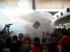 Smoke rises from a flare during scuffles between protesters and French police in front of the passport control of Terminal 2E of Charles de Gaulle Airport in Paris (Thanassis Stavrakis/AP)
