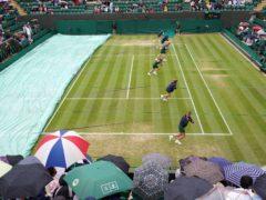 Spectators shelter from the rain on day six of Wimbledon (John Walton/PA)