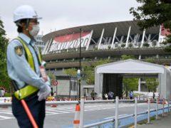 A security guard wearing face masks guards outside the National Stadium in Tokyo (Shinji Kita/AP)