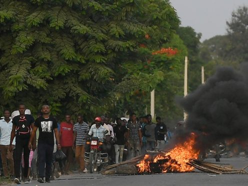 Men walk past a flaming barricade after violence broke out near the home town of late President Jovenel Moise (Matias Delacroix/AP)