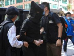 A hooded suspect is accompanied by police officers to search for evidence at an office in Hong Kong (Vincent Yu/AP)