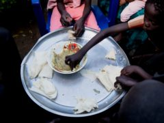 A mother shares a meal with her family at her Juba, South Sudan home (Adrienne Surprenant/PA)