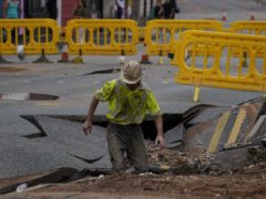 A United Utilities worker inspects the sinkhole in Green Lane, Old Swan, Liverpool (Peter Byrne/PA)