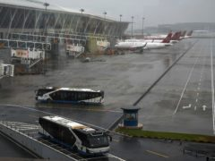 Buses and planes are parked on the tarmac after all flights were cancelled at Pudong International Airport in Shanghai, China (Andy Wong/PA)