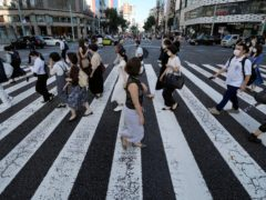People in Tokyo wearing protective masks to help curb the spread of the virus (Eugene Hoshiko/AP)