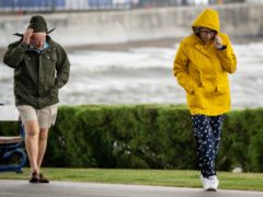 People pull down their hoods to shelter from the wind as they walk along the sea front in Porthcawl, Wales (Ben Birchall/PA).