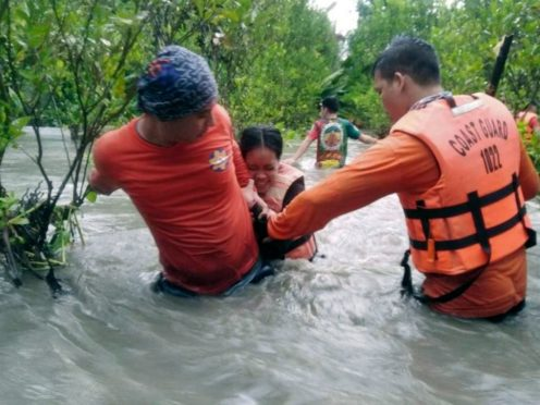 Residents wade through floodwaters as they are evacuated in Naujan, Oriental Mindoro province (Philippine Coast Guard/AP)