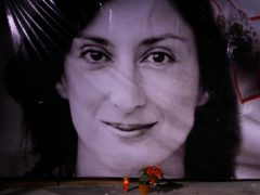 Flowers and a candle lie in front of a portrait of investigative journalist Daphne Caruana Galizia in Matla (Jonathan Borg/AP)