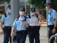 Police officers stand guard as they wait for Tong Ying-kit's arrival at a court in Hong Kong (Vincent Yu/AP)