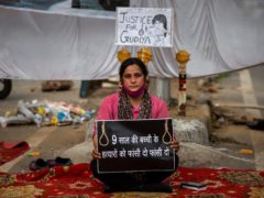 Tina Verma, 27, a social activist, holds a placard which reads: 'Hang the killers of 9-year old child' (AP)