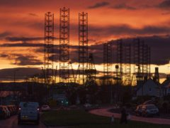 Jack-up rigs used in the North Sea oil and gas industry silhouetted against the sunset (Jane Barlow/PA)