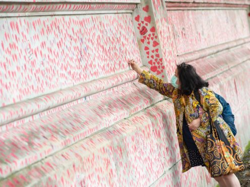 A woman writes a message on the Covid memorial wall in Westminster, London (Dominic Lipinski/PA)