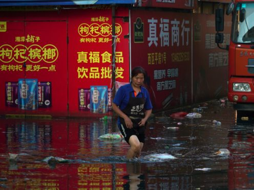 Xing, a shop owner at Yubei Agricultural and Aquatic Products World, walks in floodwaters at the market in Xinxiang in central China's Henan Province (Dake Kang/AP)