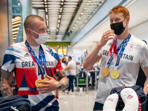British swimmers Adam Peaty (left) and Tom Dean arrive back at London Heathrow Airport (Aaron Chown/PA)