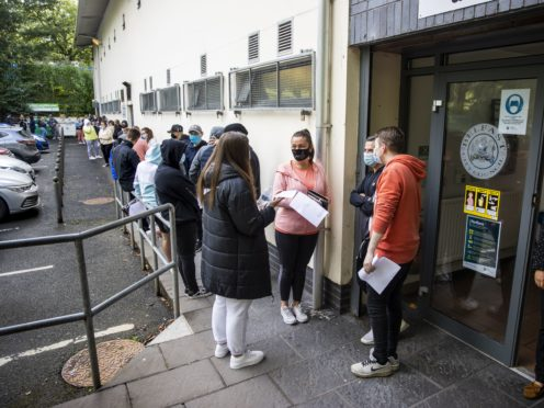 Festival goers at Feile an Phobail queuing to receive their first vaccination (Liam McBurney/PA)